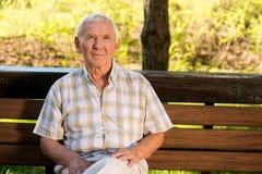 Äldre mansammanträde på bänk Royaltyfri Fotografi