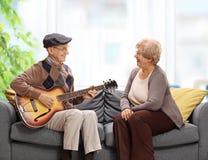 Äldre mansammanträde på en soffa och spela en gitarr till åldring royaltyfri fotografi