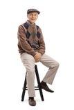 Äldre mansammanträde på en stol Royaltyfria Bilder