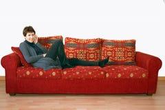 Äldre mogen kvinna som skvallrar på mobiltelefonen på soffan Arkivfoton