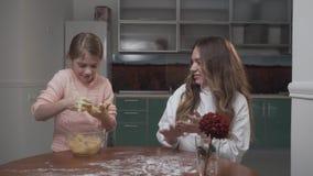 Äldre och mer ung flickor som knådar deg på en tabell i köket Två systrar förbereder grönsaksallad, medan sitta på lager videofilmer