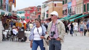 Äldre par av turister med kameror som promenerar gatan med färgrika hus i helger stock video