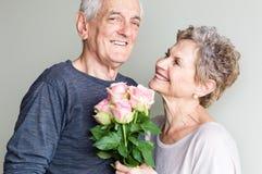 Äldre par med rosor Royaltyfri Foto