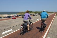 Äldre par som cyklar på Brouwersdam, Nederländerna Royaltyfri Fotografi