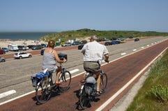 Äldre par som cyklar på Brouwersdam, Nederländerna Arkivbild