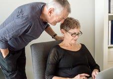 Äldre par som ser datoren Royaltyfri Foto