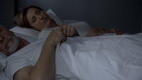 Äldre par som sover i säng, brist av sinnesrörelseproblem med styrkaklimakterium royaltyfri bild