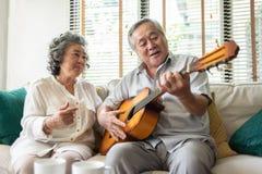 Äldre par som tycker om med att sjunga och gitarren arkivfoto