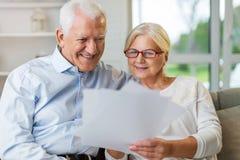 Äldre parläsninglegitimationshandlingar tillsammans på soffan fotografering för bildbyråer
