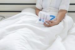 Äldre patient som använder incitamentspirometeren eller tre bollar för för att stimulera lungor i sovrum arkivbilder