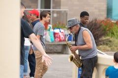 Äldre person i hatten som spelar jazz arkivbild