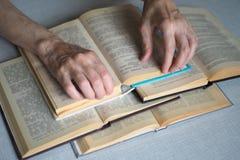 Äldre personhänder med öppnade böcker, slut upp, utvald fokus, suddighet arkivbild