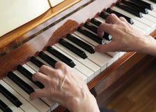 Äldre personhand som spelar pianot, slut upp royaltyfri foto