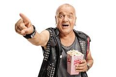 Äldre punker med en popcornask som pekar och skrattar arkivfoto