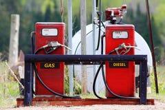 Äldre röda gaspumpar med diesel och gas Arkivfoto