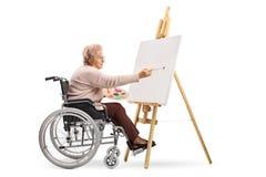 Äldre rörelsehindrad kvinna som sitter i en rullstol och målar på en kanfas royaltyfria foton