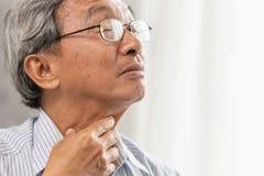 äldre retning för öm hals för gamal man och har en rörande hals för slemhand arkivfoto