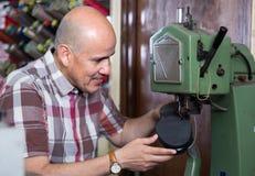 Äldre specialist som syr skor på lädersymaskinen Arkivfoto