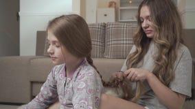 Äldre syster som hemma kammar hår av sammanträde för mer ung flicka på fluffig matta på golvet nära soffan Systerförhållande stock video