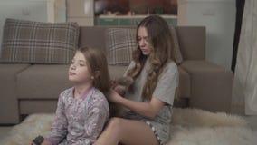 Äldre syster som kammar hår av mer ung flicka som sitter på golvet på fluffig matta nära soffan Systerförhållande lager videofilmer