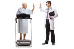 Äldre tålmodigt gå på en trampkvarn och högt-fiving en doktor royaltyfria bilder