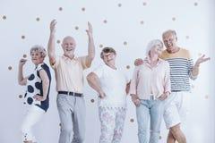 Äldre vänner som dansar och talar arkivbild