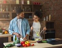 Älska afro amerikanska par som förbereder grön sallad i kök royaltyfri foto
