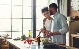 Älska afro amerikanska par som förbereder matställen i kök arkivbild