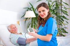 Älska anhörigvårdaren som mäter blodtryck Arkivbilder