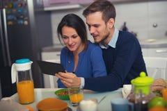 Älska barn koppla ihop i kök vid frukosttabellen i mor Arkivfoto