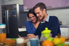 Älska barn koppla ihop i kök vid frukosttabellen i mor Arkivbild