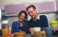 Älska barn koppla ihop i kök vid frukosttabellen i mor Royaltyfria Bilder