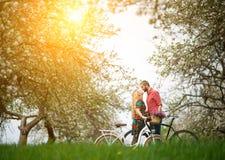 Älska barn koppla ihop med cyklar i vårträdgård arkivfoto