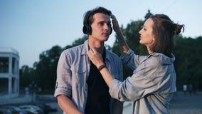 Älska barnpar i mjukt solljus för afton Flickan sätter hennes hörlurar på hennes huvud och att kyssa för pojkvän` s honom Parkera lager videofilmer
