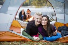 Älska barnpar som ligger i tält på Lakeshore Royaltyfri Fotografi
