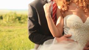 Älska brudgummen i stilyshsvartdräkten som omfamnar ömt hans härliga vit, klädde bruden utomhus Kameran lyfter långsamt arkivfilmer