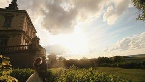 Älska brudgummen kysser hans härliga brud på solnedgången Storartad antik slott under molnig solnedgånghimmel som bakgrund arkivfilmer