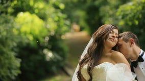 Älska brudgummen kysser skuldran av hans charmiga brud i solig sommar parkerar Precis gift par utomhus lager videofilmer