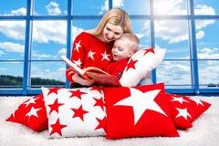 Älska den härliga barnmodern läser en bok till hans lilla son Ligga på kuddarna för inregarnering i bakgrunden av th fotografering för bildbyråer