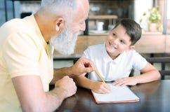 Älska den pensionerade gentlemannen som gör hem- uppgift med den lilla ungen Royaltyfri Fotografi