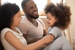 Älska den svarta familjen som kopplar av bindning i sovrum i morgonen arkivfoto