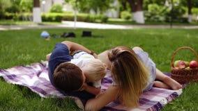 Älska den unga familjen med den lilla sonen ha en picknick utomhus Gräsplan parkerar, har picknick filten med korgen som är full  lager videofilmer