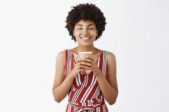 ?lska denna drink, hurra lukten av kaffe Ung kvinna f?r n?jd och gullig afrikansk amerikan med den lockiga frisyren som rymmer arkivbild