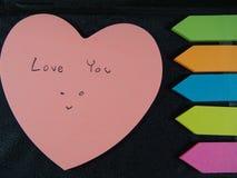 Älska dig med att le framsidan, poserar teckningen och handstil på dess papper med färgrik hjärta och pilen på svart konstläderba Royaltyfria Foton