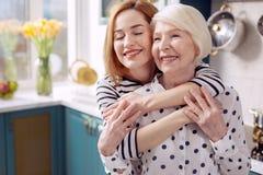 Älska dottern som ger hennes höga moder tillbaka, krama Arkivfoton