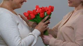 Älska dottern som gratulerar den lyckliga födelsedagen för mamma som ger blommor i tacksamhet arkivfilmer