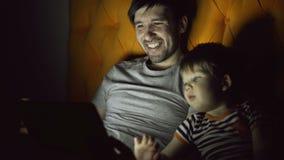 Älska fadern och hans lilla son som har online-video pratstund med morföräldrar som använder minnestavladatoren och, medan ligga, lager videofilmer