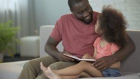 Älska fadern som håller ögonen på som hans lilla lockig-haired dotter som lär att läsa arkivfilmer