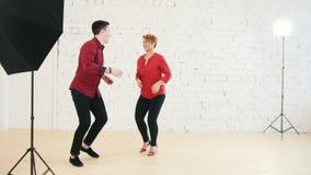 Älska familjpar i röda skjortor - kvinnlign och mannen dansar tillsammans i studio arkivfilmer