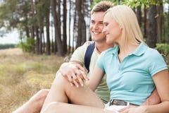 Älska fotvandra par som ler, medan koppla av i skog Fotografering för Bildbyråer